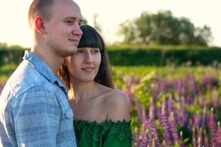 Two lovers walking among the flower meadows at sunset. The guy hugs the girl. Date, love, happiness.