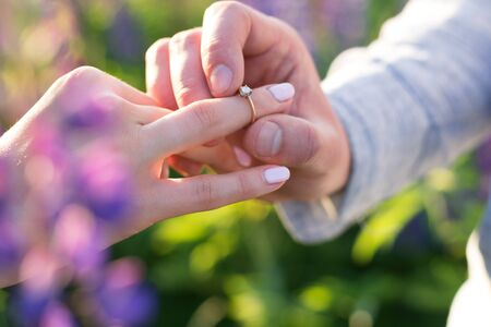 The young guy puts the ring on the finger of his beloved girlfriend. Wedding, marriage, love, union, family. Stock Photo