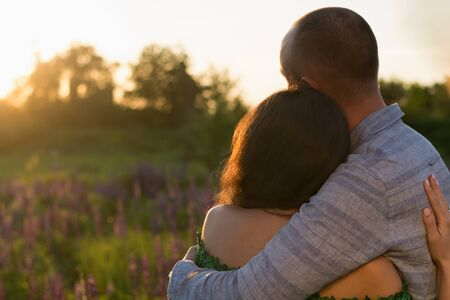 Two lovers (a boy and a girl) embrace and admire the sunset among a flower (lupins) meadow.