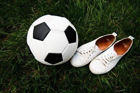 Soccer ball, grass (field), sneakers (sports shoes). Sport, competition, development, game, hobby. Фото со стока
