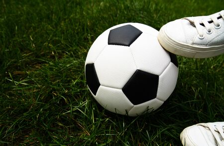 Soccer ball, grass (field), sneakers (sports shoes). Sport, competition, development, game, hobby. Stock Photo
