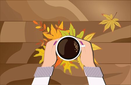 Womens hands in a woolen sweater holding a mug of hot black coffee in the autumn leaves. Food, drinks and rest.