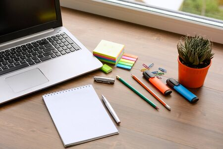 An open notebook for notes, pencils, markers, a pen, a pot with cactus, a notebook and paper clips on a wooden background (office desk). Stock Photo