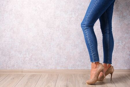A young girl in high-heeled shoes and jeans on an abstract background. Youth, parties, fashion. Stock Photo