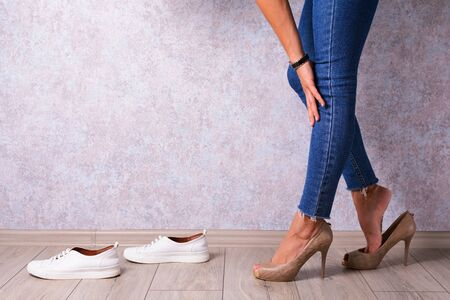 A young girl in jeans will change shoes with high heels in sneakers. Fashion, style and convenience. Stock Photo