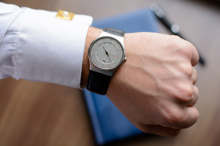 cufflinks: Hand of a man in white shirt with gold cufflinks with clock on a wooden desk with a notebook, fountain pen Stock Photo