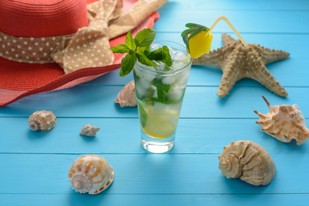 freshening: Freshening drink mohito with mint, ice and lemon on blue wooden table with seashells and summer accessories