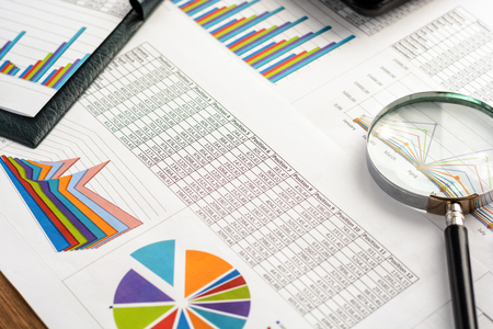 analyses: Business accessories (notebook, magnifier, calculator, planchette, tablet, fountain pen, notebook, glasses) and graphics, tables, charts on a wooden office desk. Soft focus Stock Photo