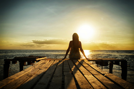 Girl in denim dress sitting on a pier on the beach and looking at the water and sun. Meditation and relaxation.