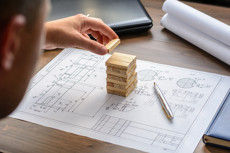 working on school project: The man (businessman, architect, designer, builder) draws a plan, graph, design, geometric shapes by pencil on large sheet of paper at office desk with diary, computer and builds model house from wooden blocks (bars)