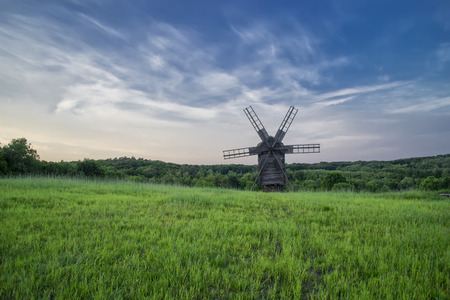 Windmills in the field under the clouds at sunset in the national museum of culture and life Pirogovo, Kiev, Ukraine, Europe