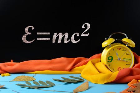 Alarm clock near a black school board, autumn leaves, scarf and an inscription e equals mc2
