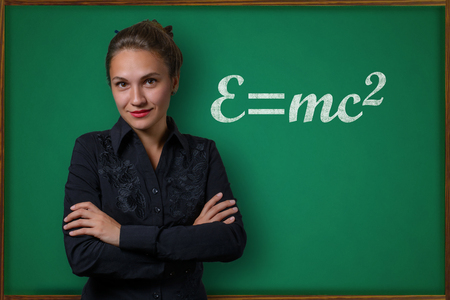 Beautiful young woman teacher (student, business woman) in classical dress standing near a blackboard with the inscription e equal mc2