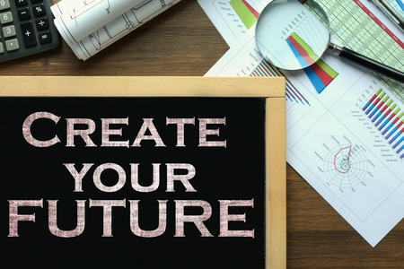 Text Create your future on the blackboard on the desk with office business accessories