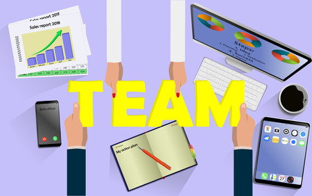 Team work concept. Top view on hands with letters TEAM above desk with laptop,mobile, tablet and other business accessories Modern business workplace