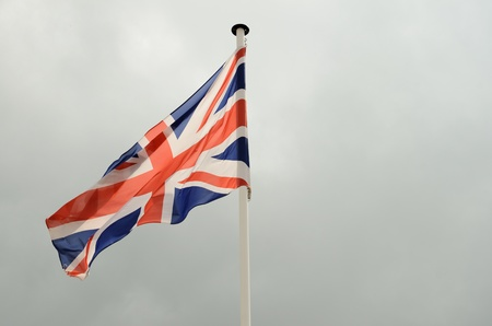 A union jack flag flying in a clear blue sky showing movement from the wind