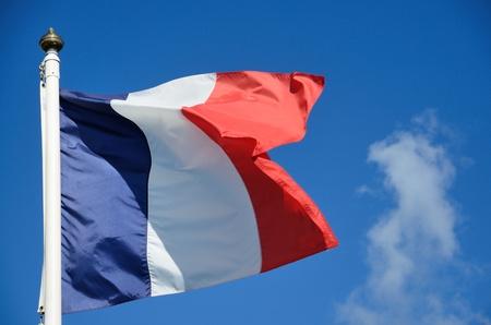 A french flag glowing o a blue sky photo