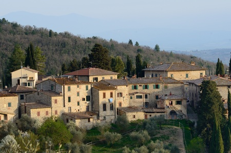 A typical tuscan village on a green hill photo