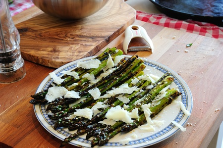 A plate of grilled asparagus with parmigiano cheese photo