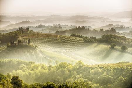 podere: A brautiful misty sun rise over the tuscan hills around San Gimignano