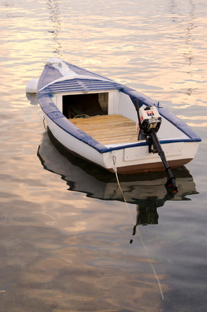 golde: The light of a sunset makes golde the sea surface around a boat