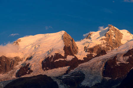 Large perspective over the French Alps and the highest peak in Europe, Mont Blanc, shortly before sunset, all being bathed in the beautiful sunset light and turning into purple