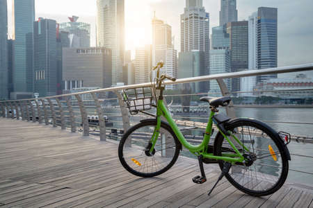 Green bike in public park and modern view business building background and sky view landscape of commercial building in central city Stock fotó