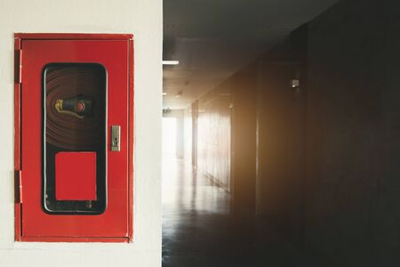 Fire extinguisher and fire hose reel in hotel , Fire safety equipment on wall cement
