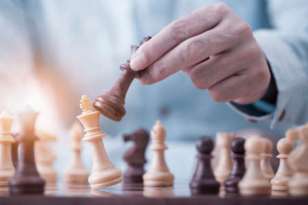 Businessman play with chess game in competition success play, concept strategy and successful management or leadership