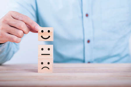 Businessman chooses a smile emoticon icons face happy symbol on wooden block , Services and Customer satisfaction survey concept