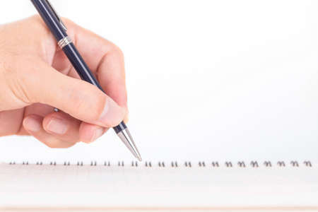 Close up of male hand with pen writing on notebook on wooden table