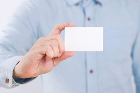 Businessman showing a blank business card on white background