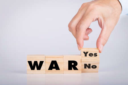 Hand holding chooses wooden block cubes with War word yes or no Archivio Fotografico