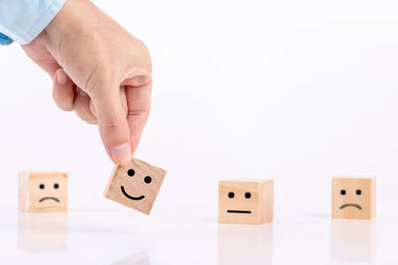 Businessman chooses a smile emoticon icons face happy symbol on wooden block , Services and Customer satisfaction survey concept Archivio Fotografico - 153174395