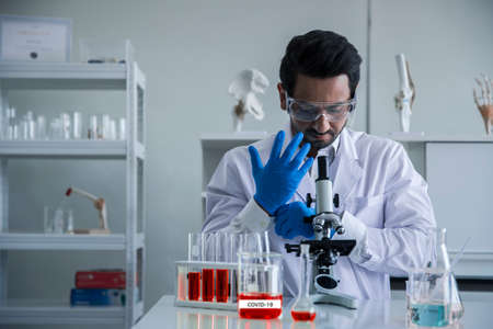 Attractive scientist medical worker with sample test tube at laboratory , doing a analysis in a laboratory doing research to create a vaccine and development Archivio Fotografico - 153763269