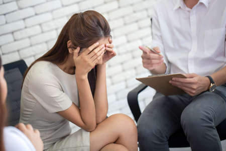 Frustrated young business woman and unhappy holding head in hands at psychotherapy session , psychiatrist making notes diary at working  office Archivio Fotografico