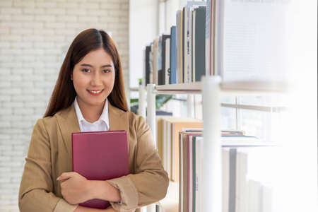 Young woman holding book in hands and smiles at a library bookshelf Archivio Fotografico - 154513155