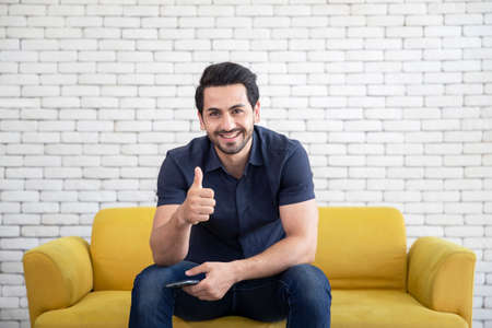 Lifestyle portrait of attractive handsome man with pleasant smile relaxing and sitting on yellow sofa at living room Archivio Fotografico