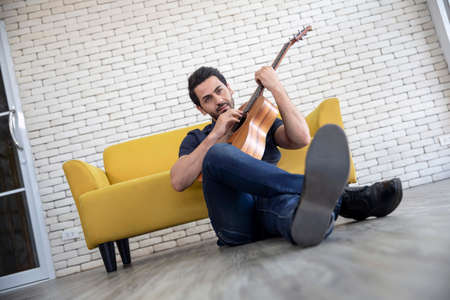 Lifestyle portrait of attractive handsome man with pleasant smile relaxing and sitting play guitar at living room Archivio Fotografico - 154513160