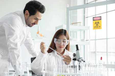 Young team scientist medical worker in lab , doing a analysis in a laboratory doing research