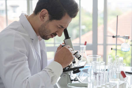 Young scientist medical worker in lab , doing a microscope analysis in a laboratory doing research