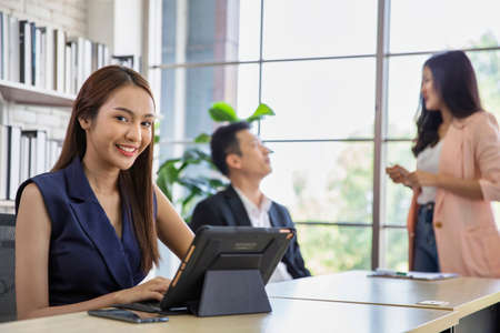 Business woman using modern digital tablet while coworker interacting in the background in the office , Teamwork meeting and partnership concept.