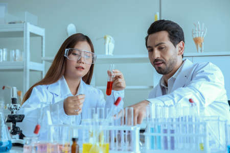 Attractive scientist medical worker with sample test tube at laboratory , doing a analysis in a laboratory doing research to create a vaccine and development Archivio Fotografico