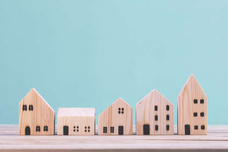Building different wood house model on blue background , managing property investment concept Archivio Fotografico - 154734532