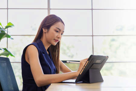 Business woman working at her office via modern digital tablet and using a digital touch screen Archivio Fotografico