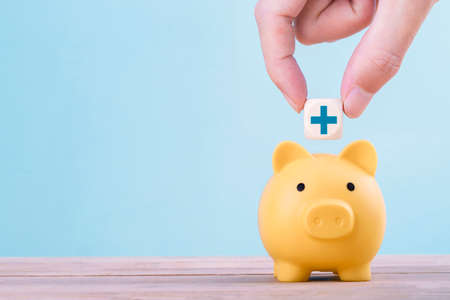 Hand putting a emoticon icons healthcare medical symbol on wooden block to yellow piggy bank , copy space for you text , Healthcare and medical Insurance concept Archivio Fotografico