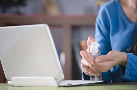 Women cleaning her hands with sanitizer gel or alcohol gel. Working from home. Protective and avoid infections corona virus Concept