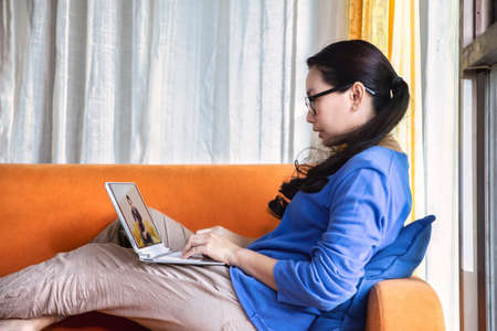 Happy young asian woman online using laptop while connection on video call at home , Asia girl speaking looking at camera talking with video call