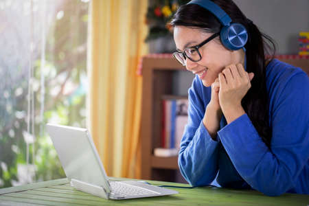 Happy young asian woman online using laptop while connection on video conference at home , Asia girl speaking looking at camera talking with video conference
