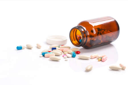 Closeup on pills capsules spilling out of pill bottle isolated on a background , Healthcare and medical drugs concept